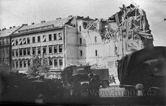 Bombardováním zřícený rohák na Václavském náměstí. Kolem ruské vozy a tanky.