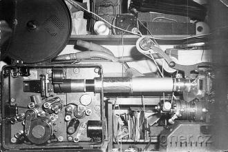 Obr.16. Asynchronní redukční kopírka z 35mm filmu 24obr/sec na 16mm film 16.obr/sec. V té tlusté trubce jsou tři objektivy.