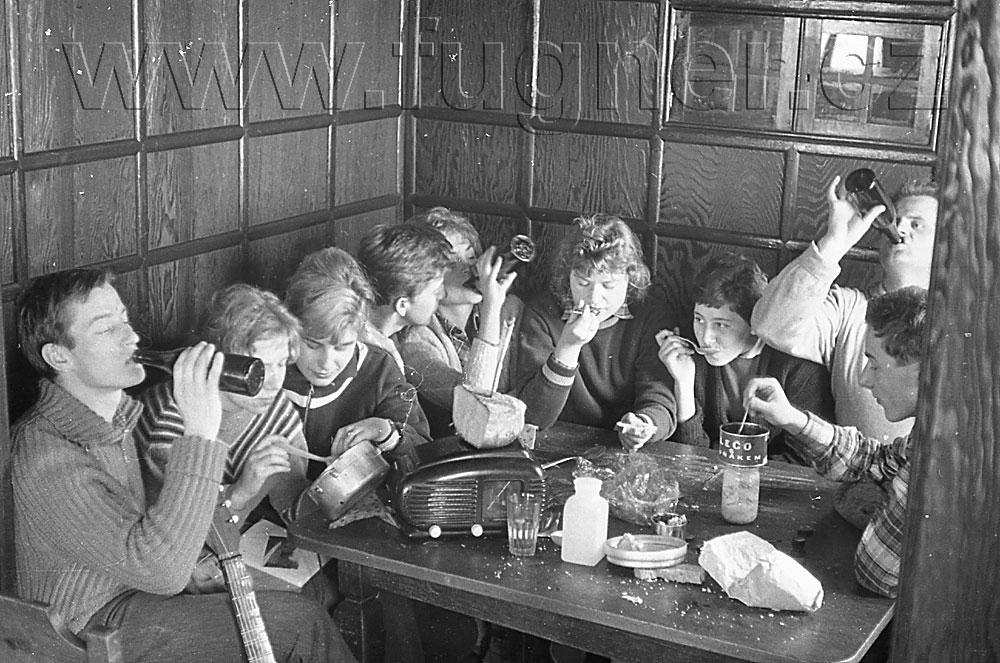 Obr. 14. Oběd vedoucích. Uprostřed hlavní vedoucí. Rozhlasový přijímač je doposud používán jako podložka- je nefunkční. Povinné školení pionýrských vedoucích, zimní Krkonoše rok 1961.