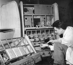 Obr. 1a. Technik Milan Fügner propojuje jednotlivé části skříně zesilovačů. Foto ČTK. Výstava Československo 1960 - Bruselský pavilon.